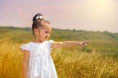 Niña linda en el vestido blanco en un campo fotografía de archivo libre de regalías