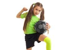 Niña linda en jugar uniforme del verde con el balón de fútbol Fotografía de archivo libre de regalías