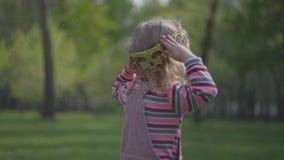 Niña linda en la corona al revés en su cabeza en el primero plano que mira adelante El jugar divertido adorable de la princesa almacen de metraje de vídeo
