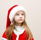 Niña linda en sombrero de la Navidad que sueña y que mira para arriba Foto de archivo libre de regalías