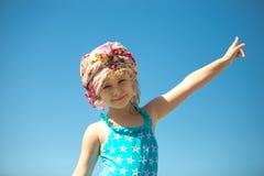 Niña linda en traje de baño contra el cielo azul Imágenes de archivo libres de regalías
