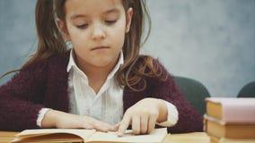 Niña linda en un fondo gris Se sienta en la tabla y lee un libro almacen de metraje de vídeo