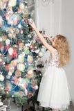 Niña linda en vestido que adorna el árbol de navidad Imagen de archivo libre de regalías
