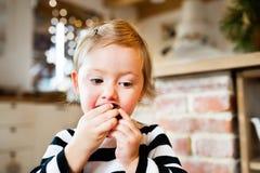 Niña linda en vestido rayado que come una galleta Imágenes de archivo libres de regalías