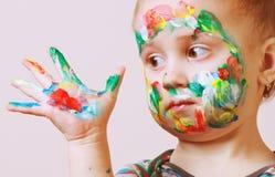 Niña linda feliz con las manos pintadas coloridas Imagenes de archivo