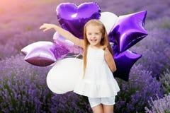 Niña linda feliz en campo de la lavanda con los globos púrpuras Concepto de la libertad Imagenes de archivo
