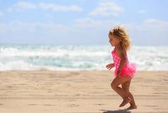 Niña linda feliz funcionada con en la playa de la arena Imagen de archivo