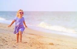 Niña linda feliz funcionada con en la playa de la arena Foto de archivo libre de regalías