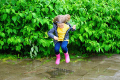 Niña linda feliz que salta en charco después de lluvia en verano Fotos de archivo libres de regalías