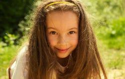Niña linda feliz que se divierte en el parque Foto de archivo