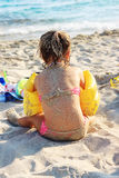Niña linda feliz que se sienta en la playa del mar caliente en el Summ Imagenes de archivo