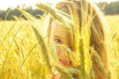 Niña linda feliz que sonríe en el campo en la puesta del sol Muchacha feliz en la naturaleza Imágenes de archivo libres de regalías