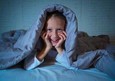 Niña linda hermosa en cama debajo de la manta que considera alegre y feliz la hora de acostarse fotos de archivo