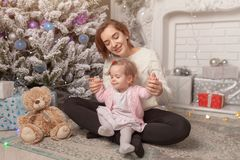 Niña linda hermosa que se sienta en el piso cerca del árbol del Año Nuevo al lado de su madre imágenes de archivo libres de regalías