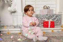 Niña linda hermosa que se sienta en el piso cerca del árbol del Año Nuevo Humor del día de fiesta, espontaneidad infantil y atmós imágenes de archivo libres de regalías