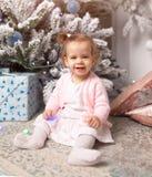 Niña linda hermosa que se sienta en el piso cerca del árbol del Año Nuevo Humor del día de fiesta, espontaneidad infantil y atmós fotos de archivo