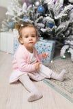 Niña linda hermosa que se sienta en el piso cerca del árbol del Año Nuevo Humor del día de fiesta, espontaneidad infantil y atmós foto de archivo