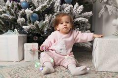 Niña linda hermosa que se sienta en el piso cerca del árbol del Año Nuevo Humor del día de fiesta, espontaneidad infantil y atmós imagen de archivo libre de regalías