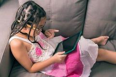 Niña linda, jugando con el ordenador en casa que pone en el sofá Imagenes de archivo