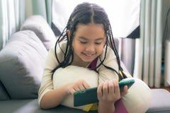 Niña linda, jugando con el ordenador en casa que pone en el sofá Fotos de archivo libres de regalías