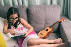 Niña linda, jugando con el ordenador en casa que pone en el sofá Imagen de archivo