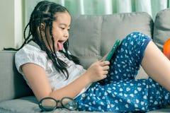 Niña linda, jugando con el ordenador en casa que pone en el sofá Foto de archivo