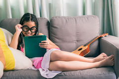Niña linda, jugando con el ordenador en casa que pone en el sofá Imágenes de archivo libres de regalías