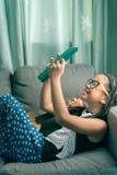 Niña linda, jugando con el ordenador en casa que pone en el sofá Fotografía de archivo