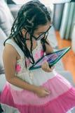 Niña linda, jugando con el ordenador en casa que pone en el sofá Foto de archivo libre de regalías