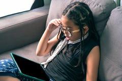 Niña linda, jugando con el ordenador en casa que pone en el sofá Fotografía de archivo libre de regalías