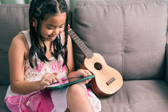 Niña linda, jugando con el ordenador en casa que pone en el sofá Imagen de archivo libre de regalías