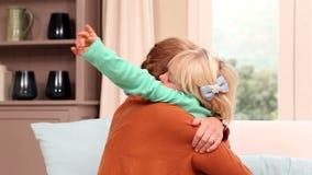 Niña linda que abraza a su madre en el sofá almacen de metraje de vídeo