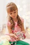 Niña linda que abre una pequeña caja de regalo en casa Luz del día de fiesta Foto de archivo