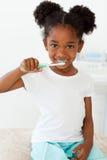 Niña linda que aplica sus dientes con brocha foto de archivo