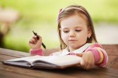 Niña linda que aprende escribir imagen de archivo libre de regalías