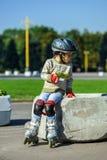 Niña linda que aprende rollerskating Foto de archivo libre de regalías