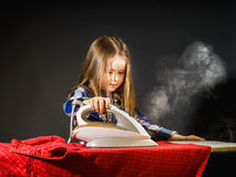 Niña linda que ayuda a su madre planchando la ropa, contras imágenes de archivo libres de regalías