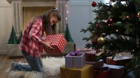 Niña linda que busca los regalos debajo de árbol de Navidad almacen de metraje de vídeo