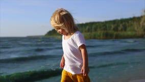Niña linda que camina a lo largo de la orilla del río A la una con la naturaleza metrajes
