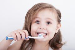 Ni?a linda que cepilla sus dientes imágenes de archivo libres de regalías