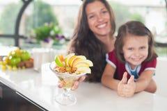 Niña linda que cocina con su hermana, comida sana Imagen de archivo libre de regalías