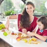 Niña linda que cocina con su hermana, comida sana Imagenes de archivo