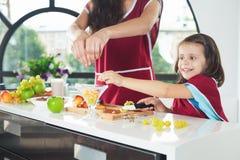 Niña linda que cocina con su hermana, comida sana Foto de archivo libre de regalías