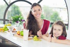 Niña linda que cocina con su hermana, comida sana Fotos de archivo
