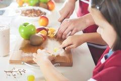 Niña linda que cocina con su madre, comida sana Fotografía de archivo