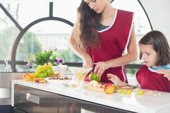Niña linda que cocina con su madre, comida sana Imagen de archivo libre de regalías