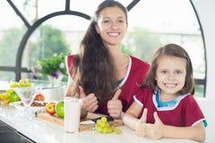 Niña linda que cocina con su madre, comida sana yogur Fotografía de archivo