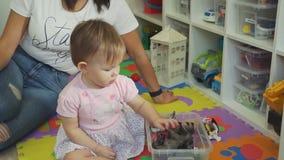 Niña linda que coge los juguetes en compartimiento plástico almacen de video