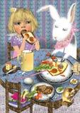 Niña linda que come al lado de un conejo del juguete Imagen de archivo