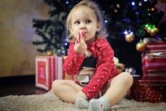 Niña linda que come el bastón de caramelo de la Navidad Foto de archivo libre de regalías